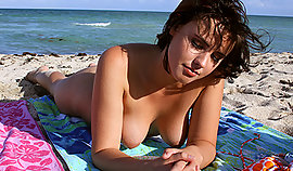 Early girl sunbaths topless on the beach